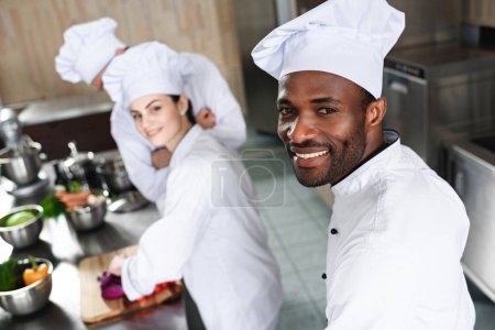 Multiracial chefs team smiling while cooking by kitchen counter