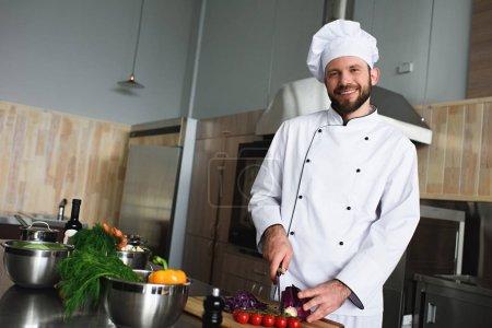 Photo pour Chef professionnel coupant des légumes sur la table de cuisine - image libre de droit