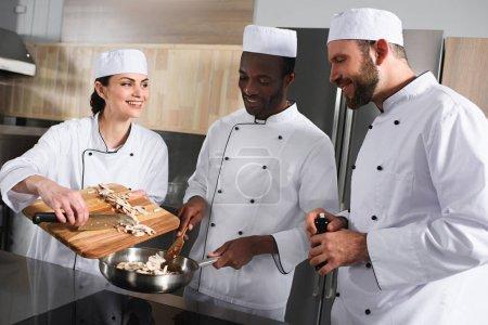 multicultural chefs preparing mushrooms at restaurant kitchen