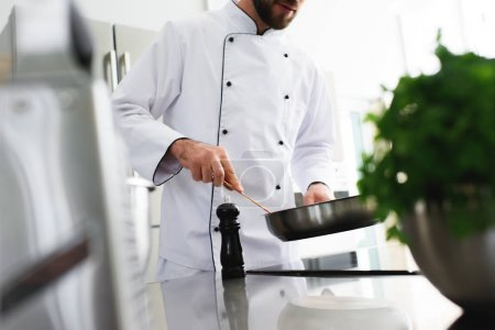 cropped image of chef frying food on frying pan at restaurant kitchen