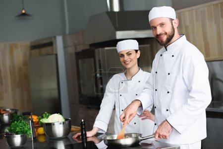 Photo pour Chefs friture légumes sur poêle au restaurant cuisine - image libre de droit