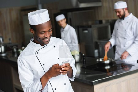 smiling african american chef using smartphone at restaurant kitchen