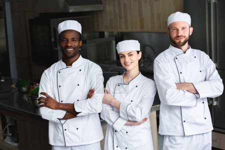 smiling multicultural chefs standing with crossed arms at restaurant kitchen