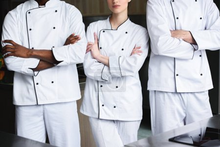 Photo pour Image recadrée de chefs multiculturels debout avec les bras croisés à la cuisine du restaurant - image libre de droit