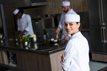 Photo pour Sourire beau chef regardant caméra à la cuisine du restaurant - image libre de droit