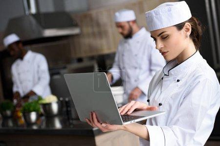 beautiful chef using laptop at restaurant kitchen