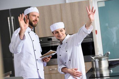 chefs waving hands at restaurant kitchen