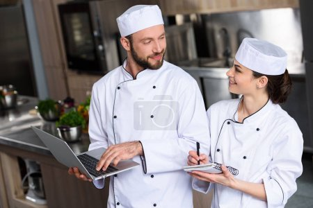 chefs using laptop at restaurant kitchen and looking at each other