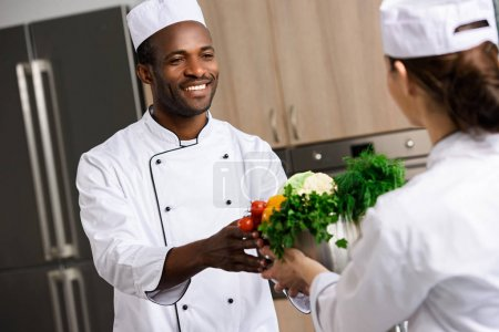 chef giving bowl with vegetables to african american colleague at restaurant kitchen