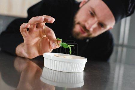 Photo pour Beau chef ajoutant du persil au plat à la cuisine du restaurant - image libre de droit