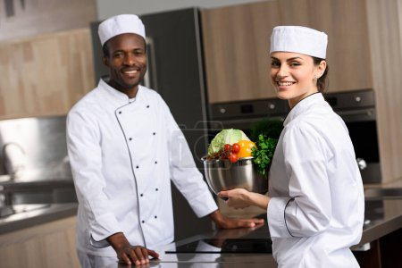 multicultural chefs holding vegetables and looking at camera at restaurant kitchen