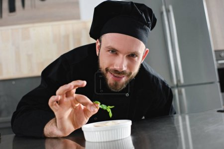 handsome chef adding herb to dish at restaurant kitchen