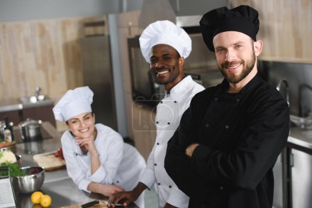 smiling multicultural chefs looking at camera at restaurant kitchen
