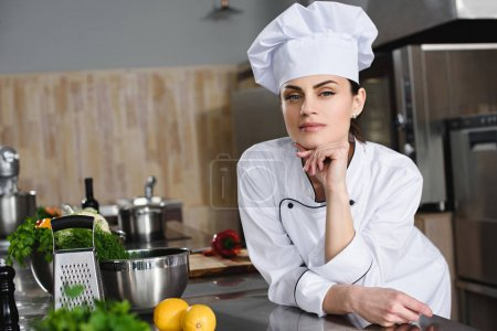 attractive pensive chef looking at camera at restaurant kitchen