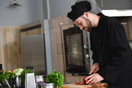 side view of handsome chef cutting bell pepper at restaurant kitchen