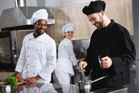 smiling multicultural chefs cooking together at restaurant kitchen