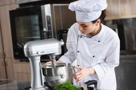 attractive chef using blender at restaurant kitchen
