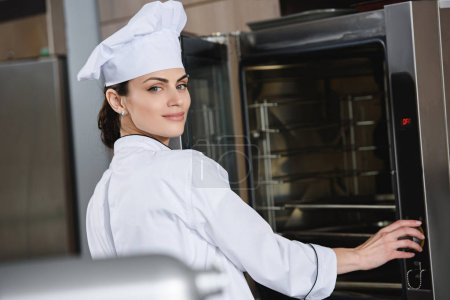 attractive chef standing near oven at restaurant kitchen