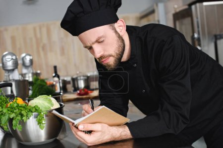 side view of handsome chef writing down new recipe to notebook at restaurant kitchen