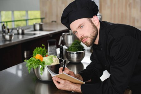 handsome chef writing down new recipe to notebook at restaurant kitchen and looking away