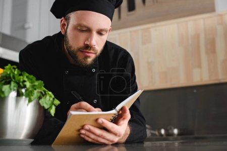 Photo pour Beau chef écrivant nouvelle recette pour ordinateur portable à la cuisine du restaurant - image libre de droit