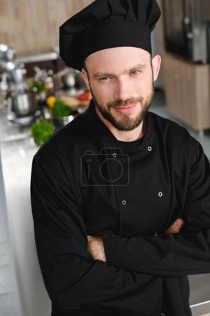handsome chef standing with crossed arms and looking away at restaurant kitchen