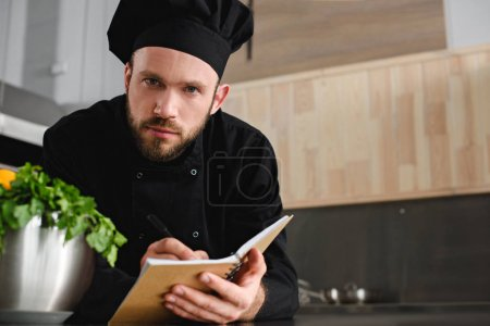 handsome chef writing down new recipe to notebook at restaurant kitchen and looking at camera