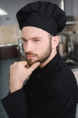 pensive handsome chef looking away at restaurant kitchen