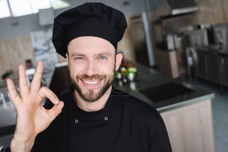 smiling handsome chef showing okay gesture at restaurant kitchen