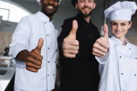 cropped image of smiling multicultural chefs showing thumbs up at restaurant kitchen