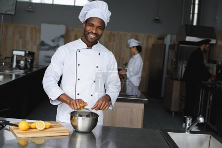 smiling handsome african american chef squeezing lemons at restaurant kitchen