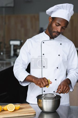 handsome african american chef squeezing lemons at restaurant kitchen