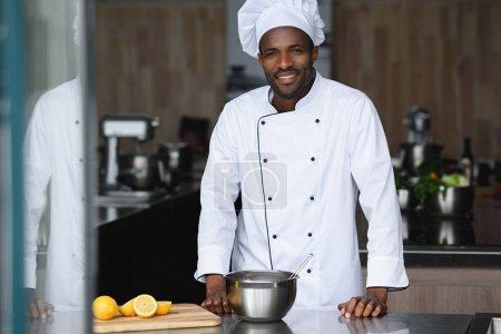 handsome african american chef standing near kitchen counter at restaurant kitchen