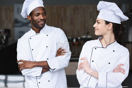 multicultural chefs looking at each other at restaurant kitchen