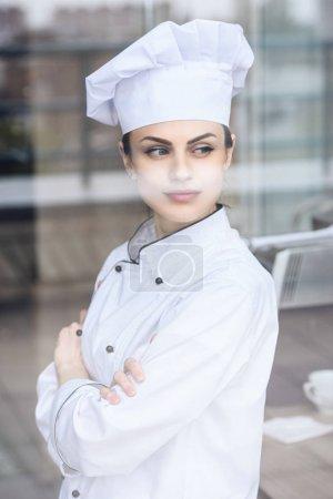 attractive chef looking away at restaurant kitchen