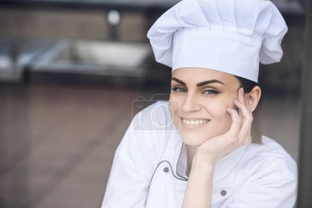smiling attractive chef looking at camera at restaurant kitchen