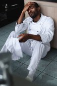 exhausted african american chef sitting on floor at restaurant kitchen