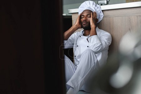 tired african american chef sitting on floor at restaurant kitchen