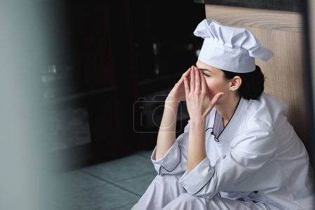 side view of chef crying and sitting on floor at restaurant kitchen