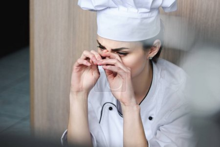 chef crying and sitting on floor at restaurant kitchen
