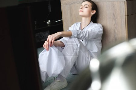attractive tired chef sitting with closed eyes on floor at restaurant kitchen