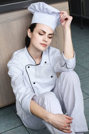 attractive chef sitting on floor at restaurant kitchen