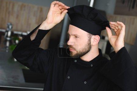 handsome chef wearing hat at restaurant kitchen