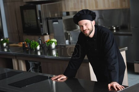 handsome chef looking at camera at restaurant kitchen