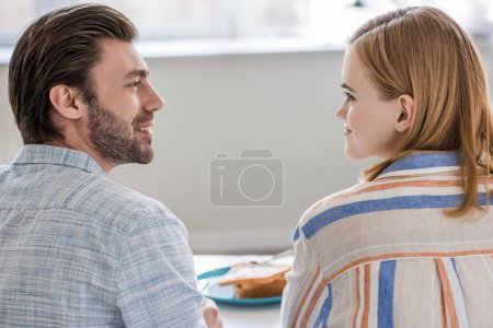 young couple sitting at table and looking at each other during breakfast time