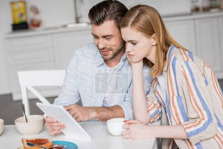 smiling man using digital tablet with attractive girlfriend at table with breakfast