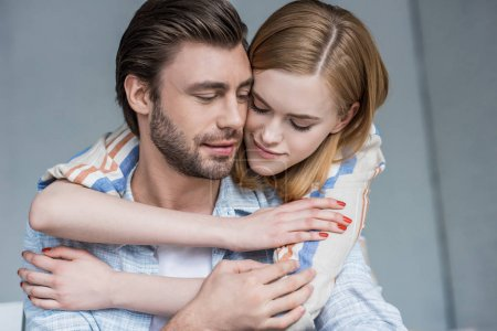attractive young woman hugging boyfriend from behind