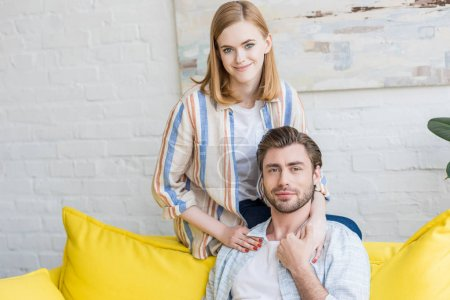 smiling young woman sitting on edge of couch and embracing boyfriend