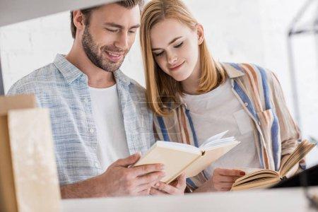 Photo pour Souriant jeune femme regardant petit ami livre - image libre de droit