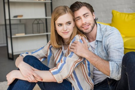 stylish young couple sitting on floor in living room